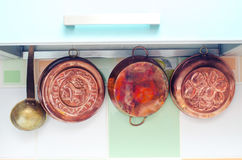 Copper kettles. Vintage copper kitchenware on the wall Royalty Free Stock Photo