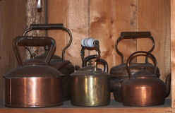 Copper Kettles. Copper and brass kettles sitting on shelf Stock Photography