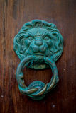 Copper lion door knocker on a wooden door. Ancient lion shaped Copper door knocker on a wooden door. Concept of entrance stock photo