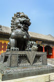 Copper lion in front of an ancient architecture in summer palace Royalty Free Stock Photo