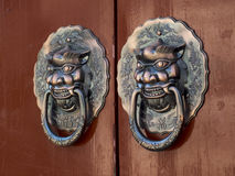 Copper lion handle. Two bronze lions on the door handle China Royalty Free Stock Photo