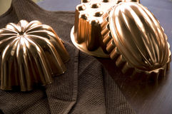 Copper molds on wooden table Royalty Free Stock Image