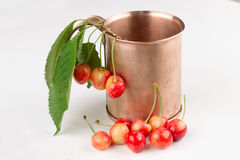 COPPER MUG with white cherries on a white background Royalty Free Stock Photo