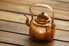 Copper old scratched vintage crockery kitchenware kettle on the table royalty free stock images