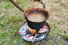 Copper pan on fire with soup during a Middle Ages historic reenactment.  stock images
