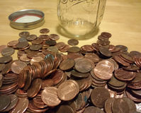 Copper Pennies, American Money, Spare Change, One Cent Coins, Coin Collecting. An empty Mason jar sits near hundreds of pennies waiting to be sorted, counted Royalty Free Stock Photo