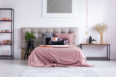 Homely bedroom with copper phone. Copper phone and accessories on shelf in homely bedroom with pink overlay on king-size bed stock images