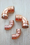 Copper pipe elbows. Copper pipe elbow fittings of different sizes used for plumbing work on domestic water supply with copper pipe work stock photos