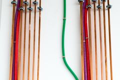 Copper pipes and colorful plastic tubes for electrical wiring on a white wall. At an unfinished building site royalty free stock image