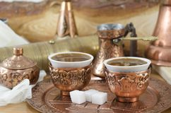 Copper plates and cups filled with coffee Royalty Free Stock Image