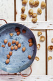 Copper pot with apricot pits. Apricot pits in a copper pot on a wooden old table Royalty Free Stock Image