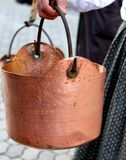 Copper pot carried by a peasant woman to the rural village Stock Images