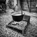 Copper pot hanging over the fire to heat water. Royalty Free Stock Photos