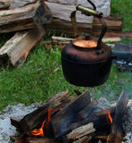 Copper pot hung over a camp fire Stock Image