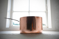Copper pot on the window frame Stock Photography