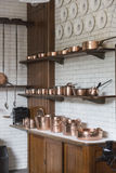 Copper pots, pans, saucepans and utensils in an old-fashioned kitchen. Shiny copper pots, pans and saucepans and other utensils arranged on shelves in an old Royalty Free Stock Photo