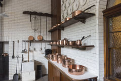 Copper pots, pans and saucepans in a vintage kitchen Royalty Free Stock Photos