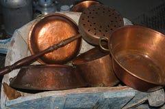 Copper pots in a wheelbarrow. Some copper pots in a wheelbarrow Royalty Free Stock Photo