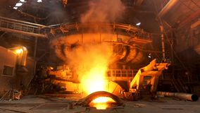 Copper production at the metallurgical plant, dangerous work concept. Stock footage. Molten metal in a huge industrial. Copper production at the metallurgical stock photography