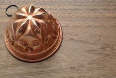 Copper pudding mould. On wooden top Royalty Free Stock Photos