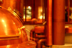 A copper red beer tank with a handle and a lid. With a column in the background royalty free stock image