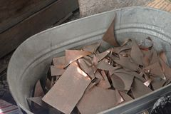 Copper scraps in tin bucket. Copper scrap metal in tine bucket in blacksmith workshop royalty free stock photos
