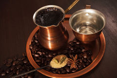 Copper set for making turkish coffee with spices coffee is ready to be served. Still life, a copper coffee set consisting of a plate, a cezve, which is a turkish royalty free stock image