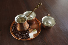 Copper set for making turkish coffee with spices. Still life, a copper coffee set consisting of a plate, a cezve, which is a turkish coffee pot, and a cup. There Stock Photos