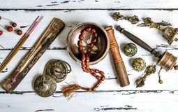 Tibetan religious objects for meditation and alternative medicin. Copper singing bowl, prayer beads, prayer drum, stone balls and other Tibetan religious objects Stock Photo