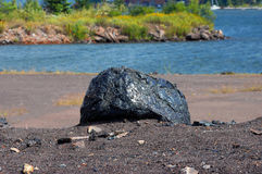 Copper Slag Rock. Former copper mining area has remnants of industry in the form of a large, copper slag rock on shore of Portage Lake.  Beach is near Hancock Royalty Free Stock Photography