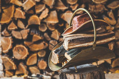 Copper stack of standing on stump in her firewood, hat. Copper stack of firewood and leather hat standing on a tree stump in front of stacked logs stock photo