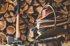 Copper stack of standing on stump in her firewood, hat. Copper stack of firewood and leather hat standing on a tree stump in front of stacked logs. Nearby is an stock images