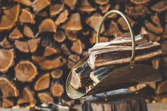 Copper stack on tree stump in front of stacked firewood. Copper stack of firewood standing on a stump in the background of folded logs stock photography