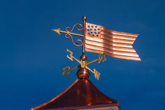 Copper Stars and Stripes Weathervane. Freshly crafted copper American flag and brass weathervane installed above copper roof Royalty Free Stock Photo