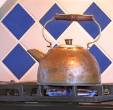 Copper tea kettle. On gas stove with ceramic tile background Stock Photography