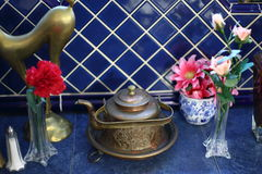 Copper teapot with decorations. A copper teapot with flowers with the blue tiles background Stock Photo