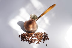 Copper turkish coffee pot with bunch of roasted coffee beans. An old Ibrik. Copper turkish coffee pot, with a wooden handle in morning sunlight on light stock photo