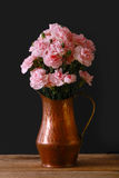 A copper vase on a black background with pink miniature carnations. Pink miniature carnations on a black background with a wood floor and dramatic lighting Stock Photos
