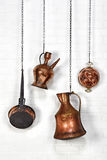 Copper ware hanged on white brick wall. Four similar item together hanged with chain. A frying pan, a jug, a pitcher and an egg pan Royalty Free Stock Images