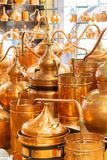 Copper ware, serpentine and jugs on the shop window in the store. Many copper vessels glitter and brightly lit. Selective focus royalty free stock photography