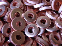Copper washers. Raw copper material punched to make washers. Bulk quantity Stock Photo