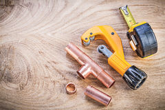 Copper water pipe cutter fittings tape measure on wood board top. View plumbing brassware concept Stock Images