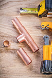 Copper water pipe cutter fixtures tape measure on wooden board v Stock Photo