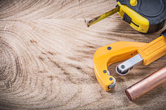 Copper water pipe cutter measuring tape on wooden board plumbing. Concept Royalty Free Stock Photo