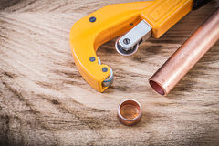 Copper water pipe cutter on wooden board plumbing brassware conc Royalty Free Stock Photo