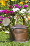 Copper watering can stands in front flowerbed Stock Photo