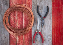 Copper wire and pliers on wood background Royalty Free Stock Images