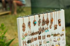Copper wire wrapped jewelry pendant on street exhibition of handmade and forged products stock images
