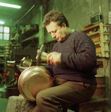 Copper worker. An artisan work copper pot in his shop in Italy Royalty Free Stock Images