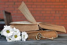 Copper wrench and two opened ancient books lying on a table of o stock photography